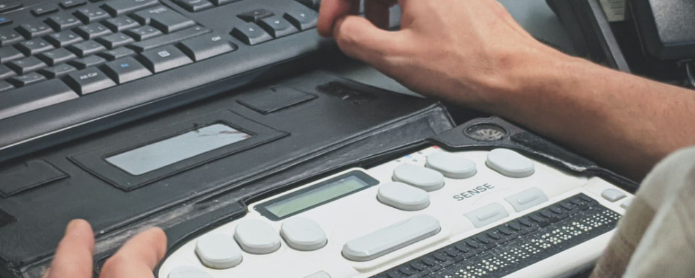 Man typing on medical equipment and keyboard