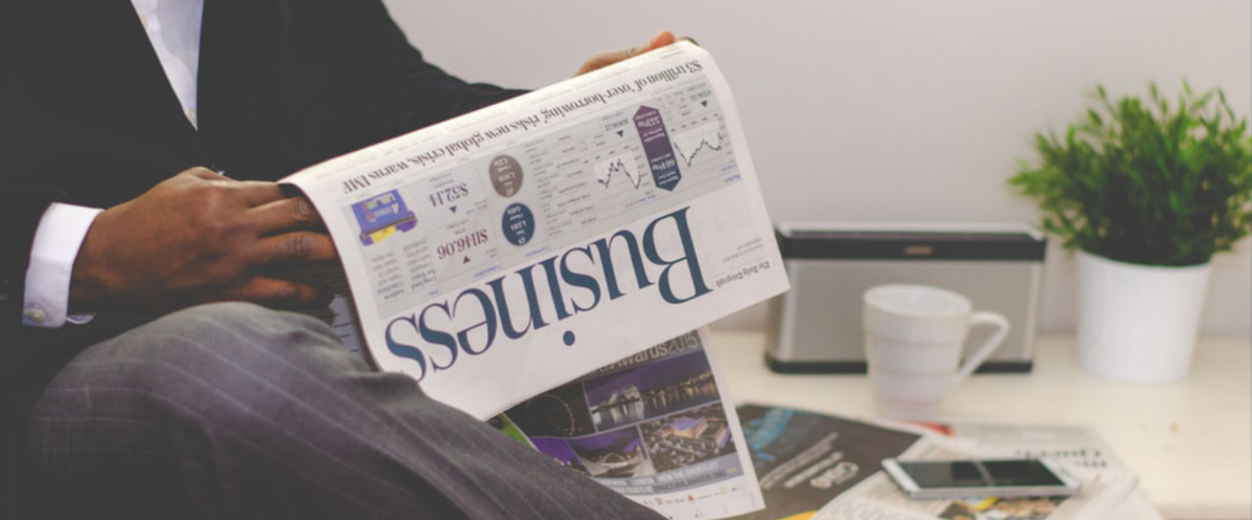 Man in a suit reading a business newspaper