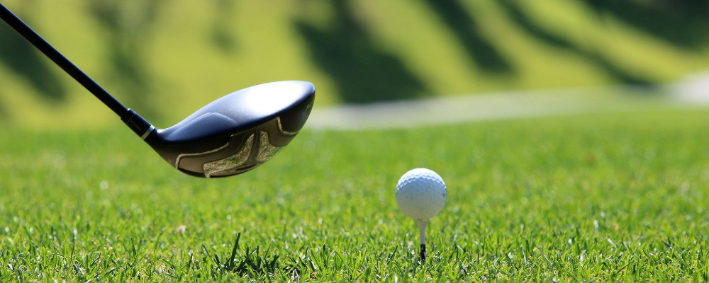 Golf putter swinging toward golfball