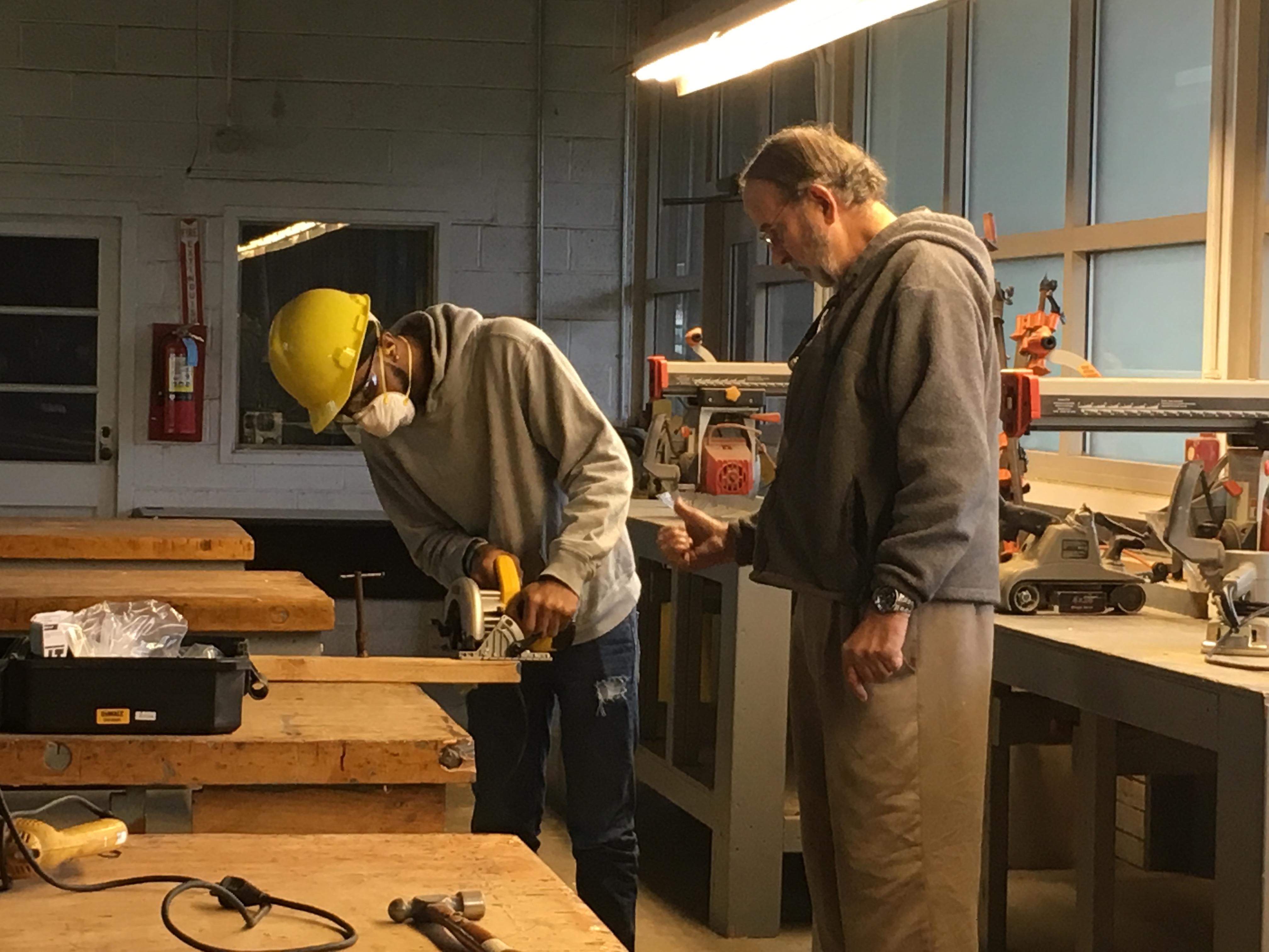 Instructor working with student on usuing a table saw