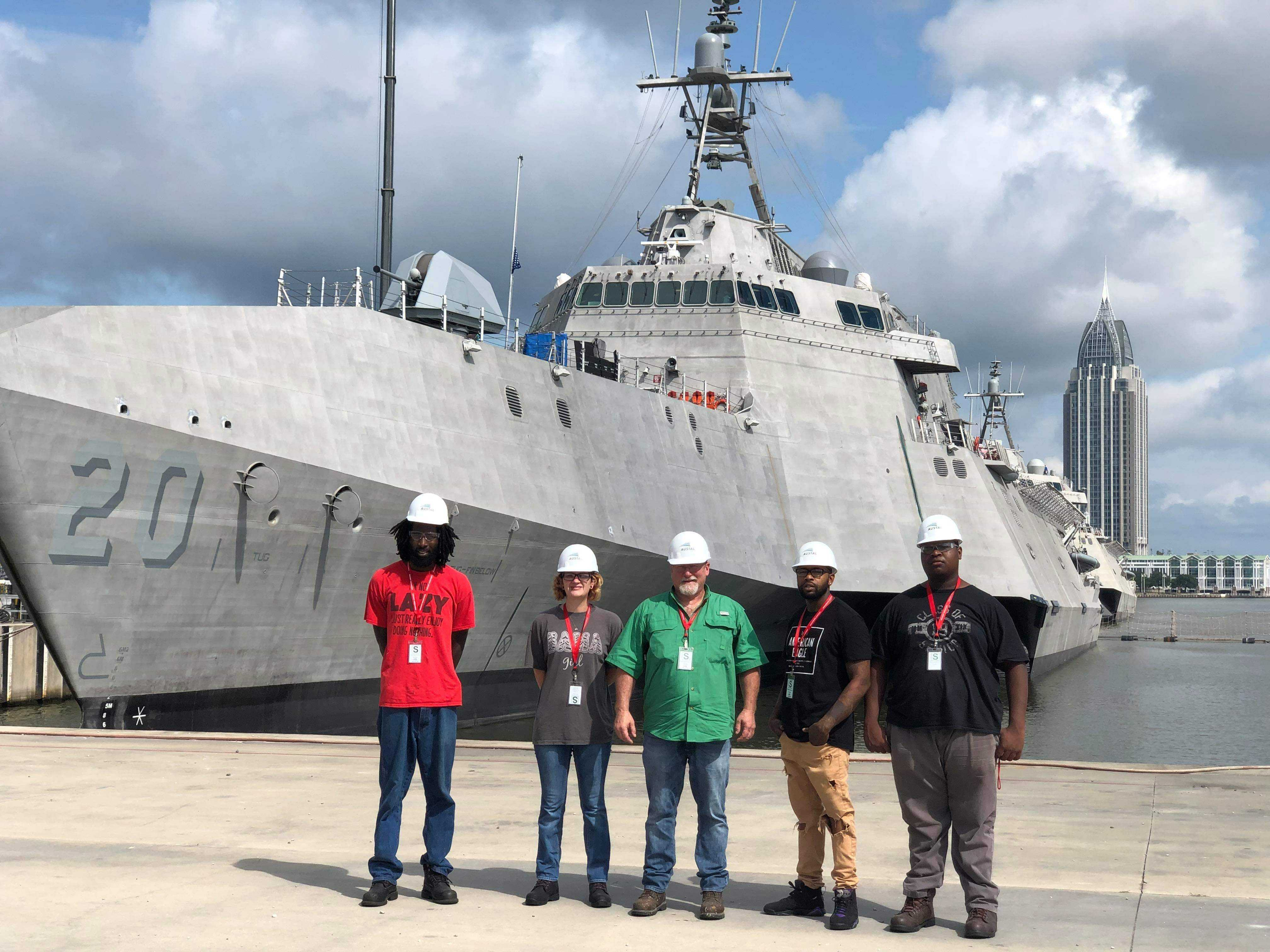 Welding students standing in front of a battleship at Austal