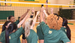 women's volleyball team in a huddle