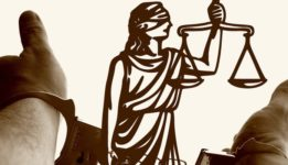 Hands in cuffs reaching out to lady justice