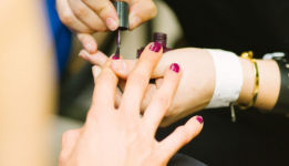Hands appling color to another persons nails