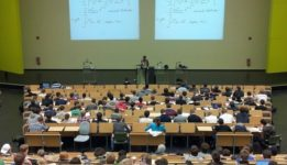 Lecture hall with students sitting at desks and  professor teaching