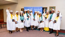 Graduates in white gowns with their arms raised