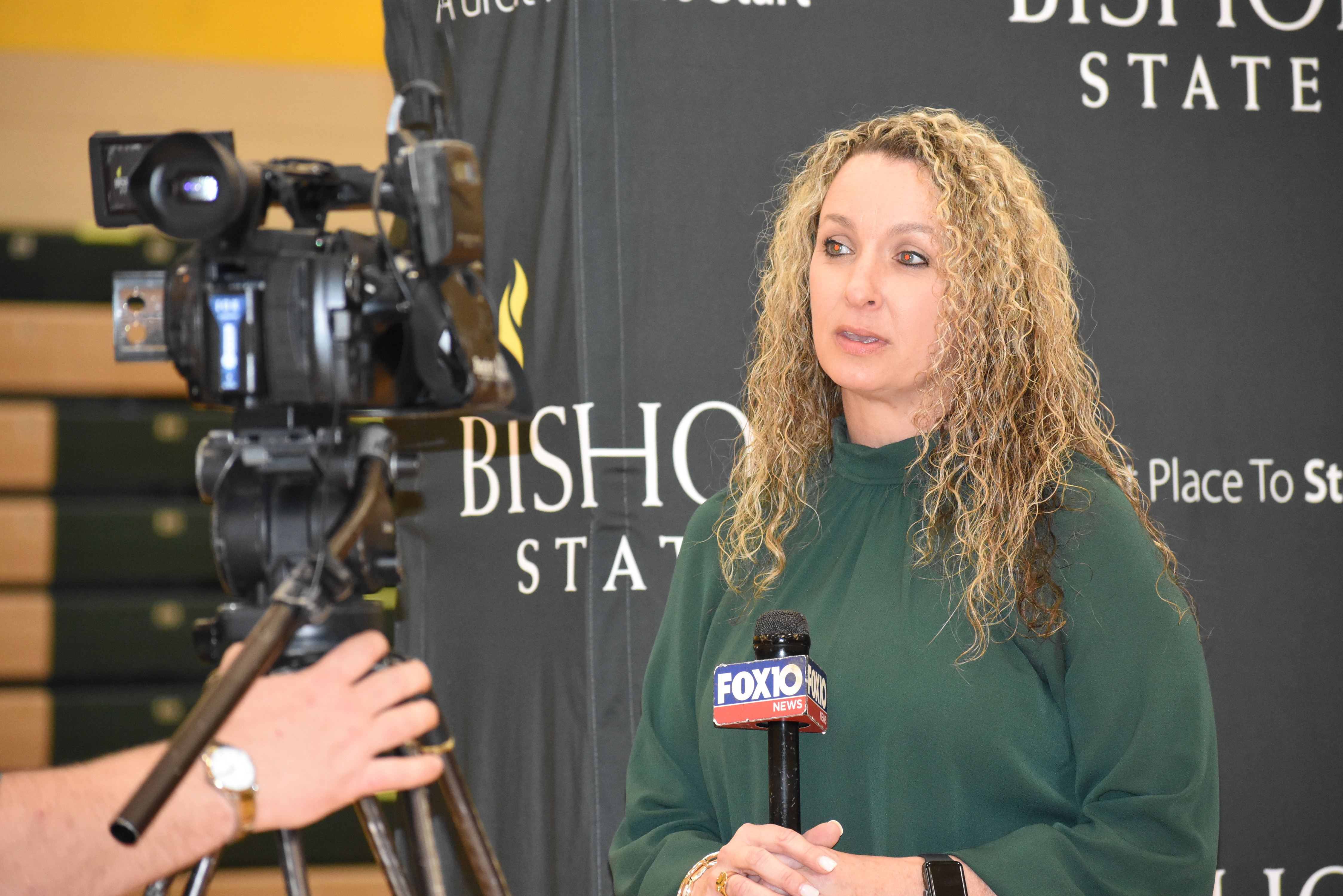 Blonde woman speaking into microphone looking at camera